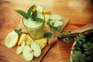 green smoothie with cut up fruit surrounding it